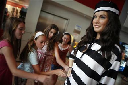 Tourists look at a wax figure of actress Lindsey Lohan dressed in ''prison stripes'' on display at Madame Tussauds Wax Museum in New York, July 25, 2007. Lohan checked in and out of jail on Thursday, spending just 84 minutes behind bars for a drunken driving and cocaine-possession conviction, Los Angeles police said. REUTERS/Brendan McDermid