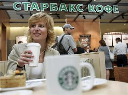 A woman drinks coffee in a newly opened Starbucks in a mall in Khimki outside Moscow, September 6, 2007. Starbucks on Thursday said that for the first quarter in its history, the number of visits to its established U.S. stores fell as economic worries and two recent price hikes spooked customers, sending shares nearly 9 percent lower. REUTERS/Alexander Natruskin