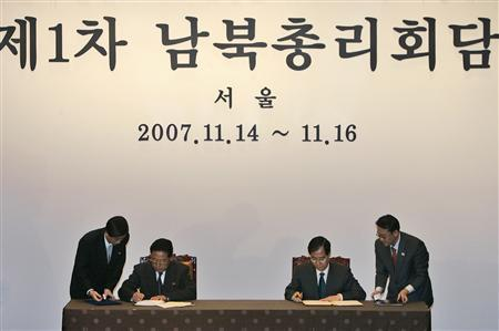 North Korean Prime Minister Kim Yong-il (L) signs joint declaration documents with his South Korean counterpart Han Duck-soo during their meeting at a hotel in Seoul, South Korea, November 16, 2007. The text on the wall translates as ''First Prime Ministers Meeting of South and North Koreas'' REUTERS/Lee Jin-man/Pool