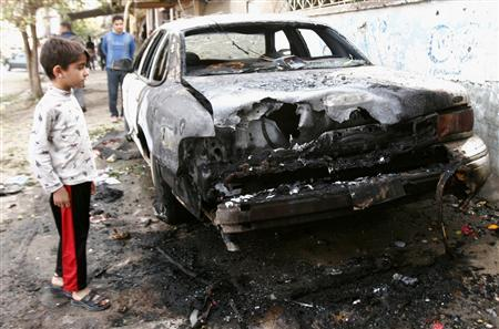 A boy looks at a burnt vehicle at the site of a bomb attack in Kirkuk, north of Baghdad, November 15, 2007. REUTERS/Slahaldeen Rasheed