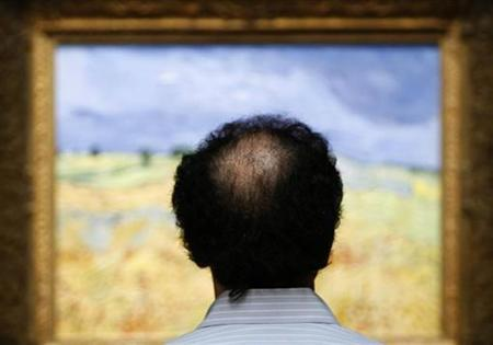 A man stands in front of a landscape by Vincent van Gogh in New York November 2, 2007. While Asian men generally have less trouble than Caucasians with the most common form of hereditary male baldness, smoking cigarettes may erase that edge, researchers said on Monday. REUTERS/Lucas Jackson