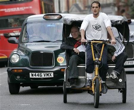 A rickshaw driver rides through the London traffic September 22, 2007. As authorities finally consider issuing licences for ''pedicabs'' after nearly a decade roaming the streets licence-free, taxi and rickshaw drivers are headed for a showdown. REUTERS/Luke MacGregor