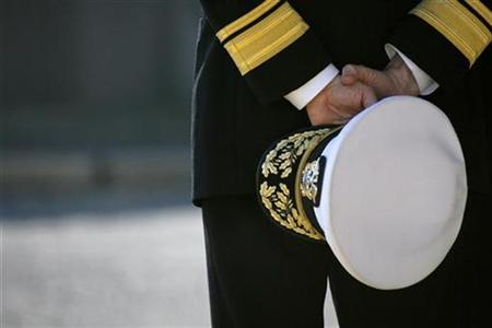 Rear admiral James Kelly, commander of U.S. Naval Base Forces Japan, holds his hat at the U.S. Naval Base in Yokosuka, February 21, 2007. Thousands of support workers at U.S. military bases in Japan went on a half-day strike on Wednesday over a Japanese government plan to cut their pay. REUTERS/Kiyoshi Ota