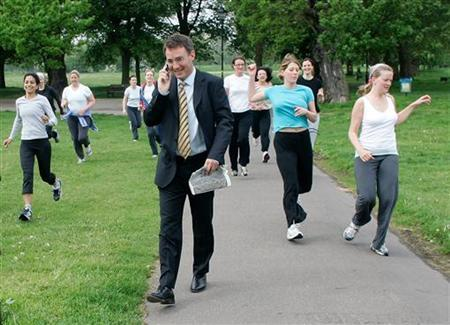 Women exercise as a man walks past on Clapham Common in London May 17, 2006. People who use a pedometer to measure how far they walk lose more weight, exercise more and have lower blood pressure than those who do not, researchers said on Tuesday. REUTERS/Kieran Doherty