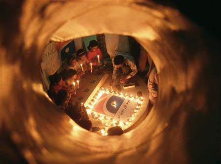Children are seen through a hole in a wall of Hyderabad's press club as they place candles around a logo of Pakistan's Geo television network in protest against media curbs imposed during emergency rule November 22, 2007. The words under the logo read, ''Live and let them live.'' REUTERS/Akram Shahid