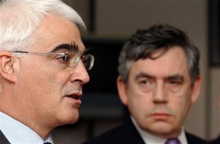 Gordon Brown (R) listens as Trade and Alistair Darling (L) speaks during a press conference at the Vauxhall plant in Ellesmere Port, northern England, May 17, 2006. Brown defended his record on Friday after an opinion poll showed public confidence in the government's competence had slumped in the wake of the lost data discs scandal. REUTERS/Nigel Roddis