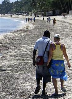 A Kenyan man walks with an unidentified tourist at the Jomo Kenyatta Public Beach in the coastal town of Mombasa November 15, 2007. Hard figures are difficult to come by, but local people on the coast estimate that as many as one in five single women visiting from rich countries are in search of sex. REUTERS/Joseph Okanga