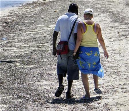 A Kenyan man walks with an unidentified tourist at the Jomo Kenyatta Public Beach in the coastal town of Mombasa November 15, 2007. Hard figures are difficult to come by, but local people on the coast estimate that as many as one in five single women visiting from rich countries are in search of sex. Picture taken November 15, 2007. To match feature KENYA-SEXTOURISM/ REUTERS/Joseph Okanga