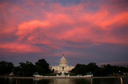 The setting sun casts an orange glow on passing clouds over the U.S. Capitol Building in Washington September 19, 2006.REUTERS/Jason Reed