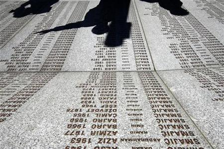 Former Dutch peacekeepers and their friends cast shadows onto the names of the Srebrenica victims as they visit their memorial in Potocari October 16, 2007. REUTERS/Damir Sagolj