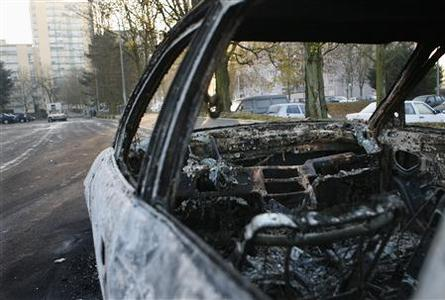 A burnt car is seen two days after the death of two youths in a motorbike accident with a police car in Villiers le Bel, northern Paris, November 27, 2007. The number of police injured in clashes in the Paris suburb overnight reached around 60, after a second night of violence. Despite appeals for calm from the victims' families, rioters torched a local library, a tax office and dozens of shops and businesses, police said. REUTERS/Charles Platiau
