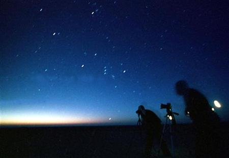 Photographers use tripods to take pictures of the night sky in a 2002 file photo. The young building blocks of galaxies similar to the Milky Way have been spotted for the first time by astronomers, giving a tantalizing glimpse of how our stellar backyard may have formed. REUTERS/Ali Jarekji