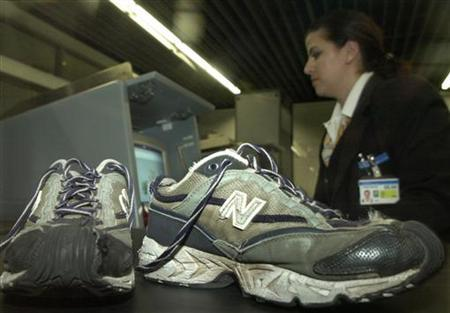 A security employee at Frankfurt airport checks a passenger's shoes with an X-ray machine December 26, 2001. Imagine a trip to the airport without having to slip off your shoes. A scanner using T-rays, a harmless form of electromagnetic radiation, could make that possible, researchers at the U.S. Department of Energy's Argonne National Laboratory said on Tuesday. REUTERS/Ralph Orlowski