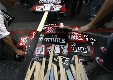 Signs are piled up at the end of a rally of striking members of the Writers Guild of America, West in Hollywood, California November 20, 2007. A televised debate set for next month among the Democratic presidential candidates will be canceled to avoid a potential conflict with striking Hollywood screenwriters, a source close to organizers said on Wednesday. REUTERS/Mario Anzuoni