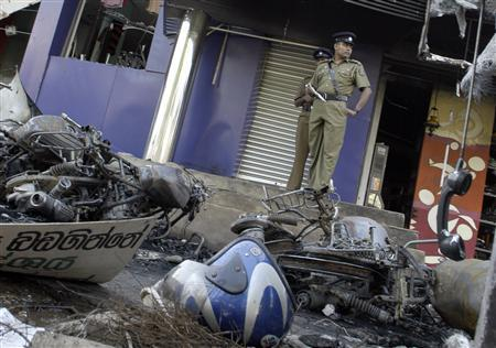 Police officers survey the scene of a bomb explosion, a day after the attack, near a shopping centre in a Colombo suburb November 29, 2007. Sri Lanka's Tamil Tigers killed 18 people in two bomb attacks in the capital Colombo on Wednesday, the military said, a day after the group's leader said he saw no hope of a peace deal to end the civil war. REUTERS/ Buddhika Weerasinghe