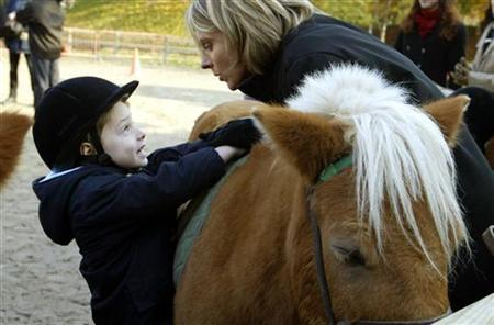 A family member speaks to an autistic child during a training session in an equestrian club in Paris, November 8, 2003. Autistic children have more gray matter in areas of the brain that control social processing and sight-based learning than children without the developmental disability, a small study said on Wednesday. REUTERS/Philippe Wojazer