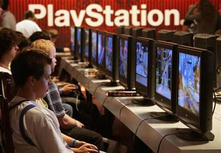 Visitors play at a Playstation exhibition stand at the Games Convention 2007 fair in the eastern German city of Leipzig August 23, 2007. Sony Corp's PlayStation 3 game console is now priced at the right level to meet the company's fiscal-year sales target of 11 million units, said John Riccitiello, chief executive officer of video game maker Electronic Arts <ERTS.O>. REUTERS/Hannibal Hanschke (GERMANY)