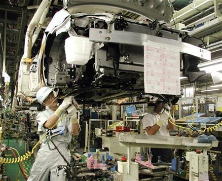 Assembly line workers install a hybrid engine into Toyota Motor Corp's new Prius sedan at Toyota's Tsutsumi plant in Toyota city, central Japan, October 2, 2003. A Toyota employee died of overwork after logging more than 106 hours of overtime in a month, a judge ruled Friday, reversing a ministry's earlier decision not to pay compensation to his widow. REUTERS/Chang-Ran Kim