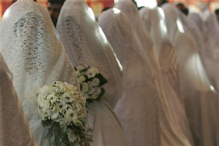Brides take part in a mass wedding ceremony in Amman, July 20, 2007. A Los Angeles company is touting a new reality game show called ''Who Wants to Marry a U.S. Citizen'' that aims to create televised matrimony between legal citizens and immigrants who have temporary visas. REUTERS/ Muhammad Hamed