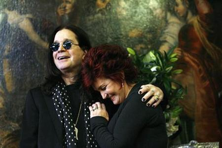 Ozzy and Sharon Osbourne smile as they pose in front of some of their belongings to be auctioned in Beverly Hills, California, November 26, 2007. The Osbournes raised more than $800,000 for charity after heavy metal enthusiasts turned out en masse for their Beverly Hills-style garage sale, auction manager Darren Julien said on Saturday. REUTERS/Mario Anzuoni