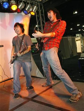 Video game enthusiasts Fredie Wong of Seattle, Washington (L) and Alex Lerner from New Jersey play Activision's ''Guitar Hero III'' at the E for All video game expo in Los Angeles, California October 19, 2007. French telecom and media group Vivendi said on Sunday it will merge its video games unit with Activision Inc in a $9.85 billion deal that combines the hit ''Guitar Hero'' and ''World of Warcraft'' franchises under one roof. REUTERS/Fred Prouser
