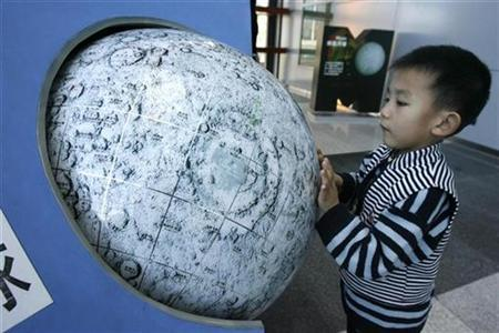 A child plays with a model of the moon displayed at Beijing Planetarium, Nov. 29, 2007. China has dismissed Internet gossip that its first photo of the moon taken from a lunar orbiter might have been plagiarised from NASA, local media said on Monday. REUTERS/Claro Cortes IV