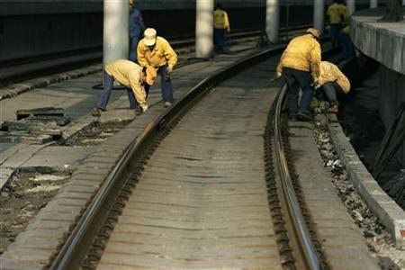 Workers maintain the tracks at a railway station in Shanghai December 3, 2007. Shares in China Railway Group, whose Shanghai IPO attracted a record 3.383 trillion yuan ($457 billion) in subscriptions, opened 56 percent higher in their debut on Monday, near the low end of analysts' forecasts. REUTERS/Aly Song