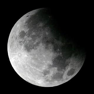 A shadow falls on the moon at the beginning of a lunar eclipse in Shanghai September 8, 2006. China has dismissed Internet gossip that its first photo of the moon taken from a lunar orbiter might have been plagiarized from NASA, local media said on Monday. REUTERS/Aly Song