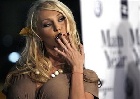 Porn actress Mary Carey blows kisses at photographers at the world premiere of ''Man of the Year'' at Grauman's Chinese theatre in Hollywood October 4, 2006. Carey, who shot to fame by running for California governor against Arnold Schwarzenegger, unveiled plans on Tuesday to auction off her autographed, recently removed breast implants for charity. REUTERS/Mario Anzuoni