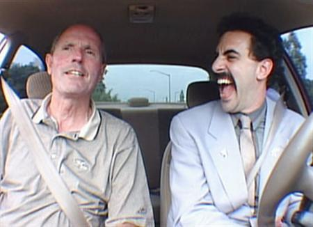 Borat (R) gets a driving lesson in the film ''Borat: Cultural Learnings of America for Make Benefit Glorious Nation of Kazakhstan'' in an image courtesy of 20th Century Fox. The creators of the hit film were sued again on Tuesday, this time by a driving instructor seen in the comedy admonishing the fake Kazakh reporter for yelling insults at other drivers. REUTERS/Handout