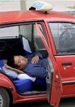<p>Un tassista di Pechino si concede una siesta dopo pranzo, 20 ottobre 2007. REUTERS/Guang Niu GN/LA</p>