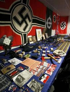 Nazi flags, seized weapons and ammunition are displayed to the press in the Portuguese police headquarters in Lisbon April 20, 2007. A left-wing German politician has filed charges against online encyclopedia Wikipedia for promoting the use of banned Nazi symbols in Germany.REUTERS/Nacho Doce