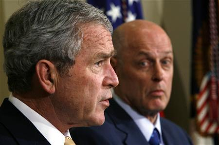 Treasury Secretary Henry Paulson glances over as President Bush speaks about his plans, aimed at slowing a wave of home loan foreclosures that has threatened to knock the economy into recession and rattled investors worldwide, from the White House in Washington, December 6, 2007. REUTERS/Kevin Lamarque