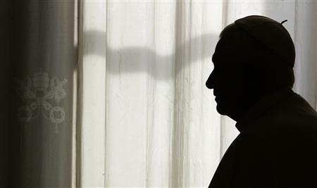 Pope Benedict XVI is silhouetted as he waits for a meeting at the Vatican, December 7, 2007. REUTERS/Tony Gentile