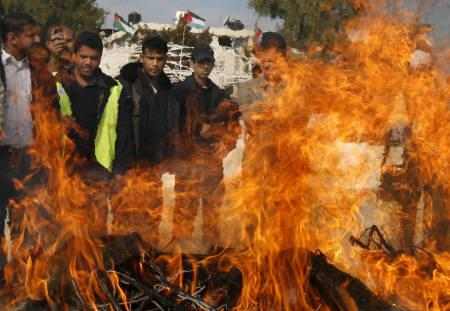 Palestinian policemen loyal to the Hamas movement burn large quantities of drugs seized from drug dealers in Gaza December 9, 2007. REUTERS/Suhaib Salem