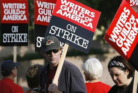 Writers Steve Tomlin (L) and Kathy McWorter walk a picket line along with members of the Writers Guild of America at one of the gates to Sony Studios in Culver City, California November 5, 2007. Hollywood screenwriters went on strike against major film and television studios on Monday, knocking some of America's favourite TV shows out of production in a dispute that hinges on how the Internet is changing the face of show business. REUTERS/Mario Anzuoni