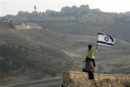 A right-wing Israeli activist holds a national flag on a hilltop near the West Bank settlement of Maale Adumim December 9, 2007. REUTERS/Gil Cohen Magen