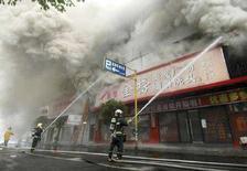 <p>Китайские пожарные тушат жилой дом в городе Вэньчжоу 12 декабря 2007 года. Пожар в жилом доме в городе Вэньчжоу на востоке Китая унес жизни 21 человека, сообщило агентство новостей China News Service на своем веб-сайте. (REUTERS/China Daily)</p>