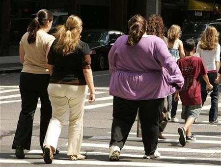 Overweight women walk across the street near Times Square in New York August 28 2007. Obesity decreases the chances that a woman will get pregnant, and the more obese she is, the worse her prospects of conception, Dutch researchers said on Tuesday. REUTERS/Lucas Jackson