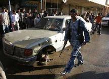 <p>Иракский солдат проходит мимо машины, поврежденной в результате взрыва бомбы в городе Амара, 12 декабря 2007 года. В результате трех взрывов в городе Амара на юге Ирака в среду погибли по меньшей мере 40 человек, десятки получили ранения, сообщил источник в полиции. (REUTERS/Atef Hassan)</p>
