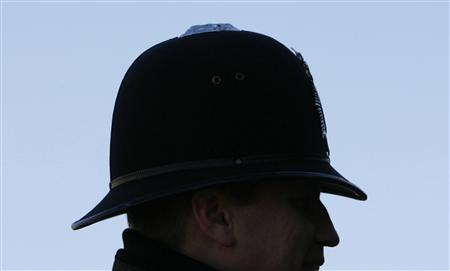 A Metropolitan police officer stands on duty outside The Houses of Parliament in central London, December 12, 2007. Police officers are to hold a crisis meeting on Wednesday to discuss possible industrial action in protest at the government's decision to stagger a pay rise. REUTERS/Toby Melville