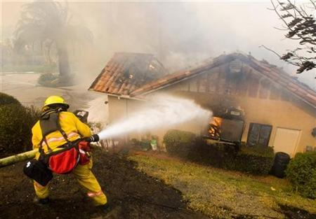 A firefighter battles a fire in a house that was in the path of a fast moving wildfire that burned through the northern part of Poway, California October 22, 2007. REUTERS/Fred Greaves