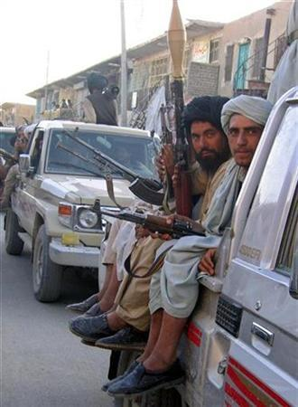 Taliban militants ride in the back of a vehicle as it drives in the Musa Qala district of southern Helmand province, November 20, 2007. Afghan and NATO-led troops killed, wounded and detained hundreds of insurgents during fighting in the Taliban's biggest stronghold, the Defence Ministry said on Thursday. REUTERS/Stringer