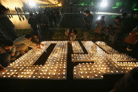 Visitors place candles to create the Chinese character ''peace'' in the new section of the Nanjing Massacre museum, as part of a ceremony marking the 70th anniversary of the Nanjing massacre in Nanjing December 13, 2007. REUTERS/ Nir Elias
