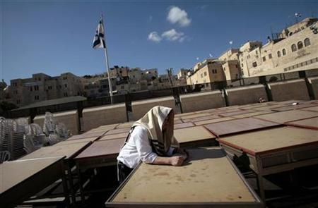 A Jewish worshipper leans on a table at the Western Wall, Judaism's holiest prayer site, in the Old City of Jerusalem, Nov. 20, 2007. A rare psychiatric disorder, caused by the intense religious energy of Jerusalem, can make a tourist of sound mind recite biblical verse on the street while claiming to be King David or Jesus. Some psychiatrists say the phenomenon, known as the Jerusalem Syndrome, causes travellers who are overcome by the spiritual magnitude of the city-- sacred to Jews, Muslims and Christians-- to believe they are prophets or characters from the bible. REUTERS/Yonathan Weitzman