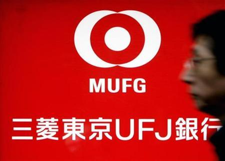 A pedestrian walks past the signboard of the Mitsubishi UFJ Financial Group (MUFG) bank branch in Tokyo, February 14, 2007. Japan's top three banks are expected to resist a request to put up a total of $15 billion for a U.S.-led subprime rescue fund, a move that could further cloud prospects for the bailout plan. REUTERS/Kim Kyung-Hoon