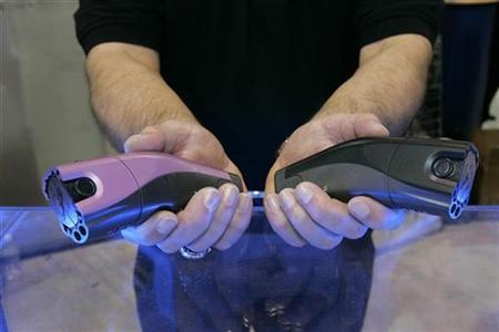A pair of Taser C2s are displayed at the Taser International booth during the 2007 International CES in Las Vegas, Nevada January 8, 2007. ''Don't Tase Me, Bro,'' a phrase that swept the nation after a U.S. college student used it seeking to stop campus police from throwing him out of a speech by Sen. John Kerry, was named Wednesday as the most memorable quote of 2007. REUTERS/Steve Marcus