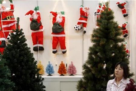 A representative from a toy factory stands next to some Christmas trees in her booth at the Shanghai Toy Expo October 18, 2007. A Chinese city has beaten the Grinch at his own game, banning Christmas trees from shopping malls, restaurants and other public places because they pose a fire hazard, a newspaper reported on Thursday. REUTERS/Nir Elias