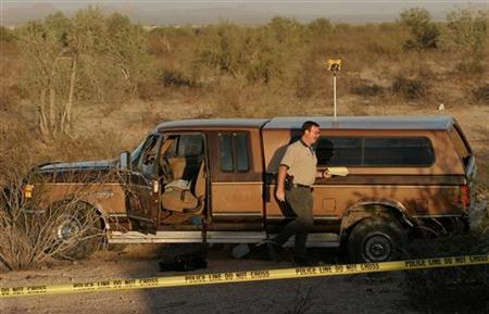 In this file photo a Pinal County Sheriff officer inspects the scene on Interstate 10 where four Mexican nationals were shot and killed approximately 25 miles south of Phoenix, Arizona, November 4, 2003. A growing number of illegal immigrants across the United States are starting to pack their bags and move on as a crackdown on undocumented immigrants widens and the U.S. economy slows. REUTERS/Jeff Topping
