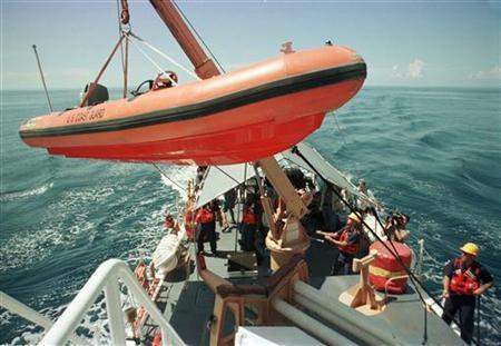 United States Coast Guard personnel on the USCGC Chandeleur prepare to deploy a zodiac boat for migrant interdiction exercises July 27, 1999 off the Miami coast. Four times Maria Galban's brother Jorge tried to make the clandestine trip from Cuba to Florida and failed. Now his family fears a fifth attempt to migrate may have ended with him losing his life at sea. REUTERS/Colin Braley